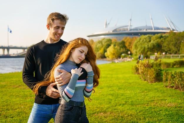 長い赤い髪の美しい若いカップルの男性と女性は、に対して都市公園の抱擁に立っています