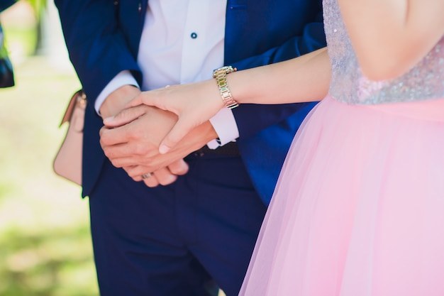 Beautiful young couple a man and a woman. close-up hand of groom and bride with a wedding ring. focus on the arm and the ring. bride in white dress. the picture is cropped without faces.