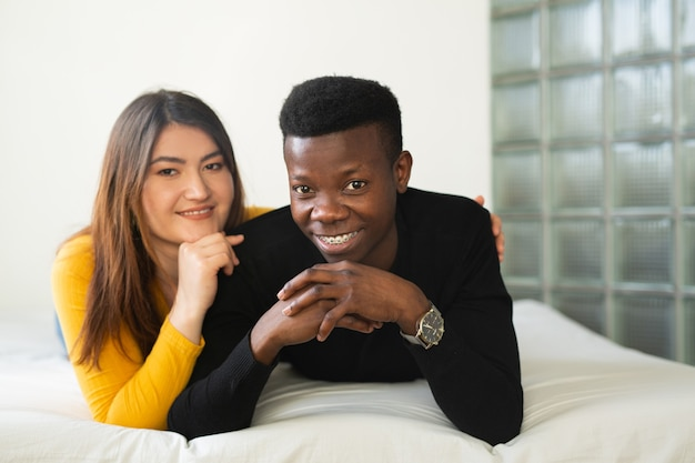 Beautiful young couple man and woman indoors on bed