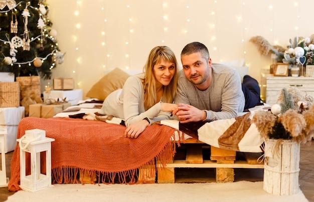 クリスマスツリーの近くの美しい若いカップル。かわいい家族はクリスマスを祝います。