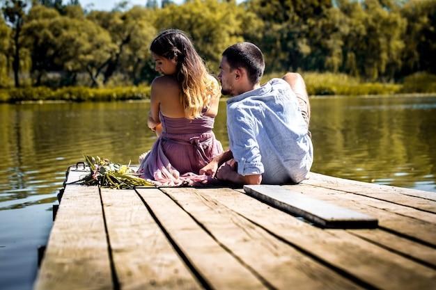 川の近くの桟橋で美しい若いカップル