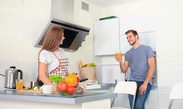 Beautiful young couple in pajamas is looking at each other and smiling while cooking in kitchen at home.