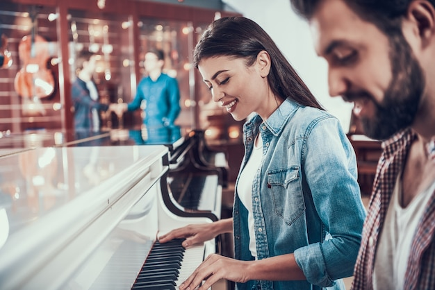 Beautiful young couple playing piano together in music store.
