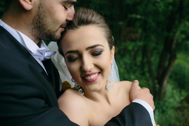 Beautiful young couple posing in the forest from close angle