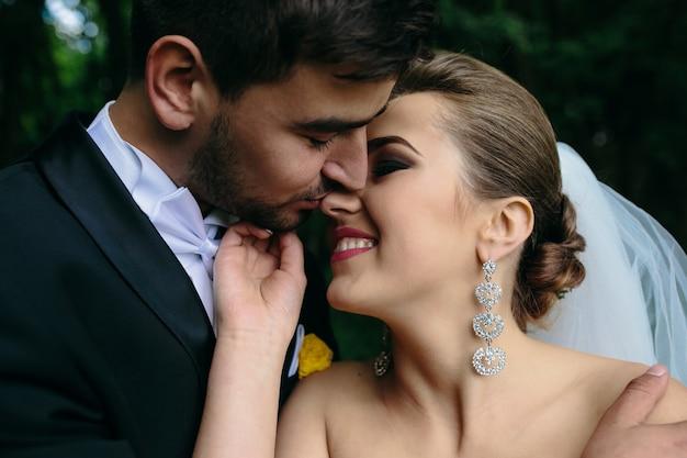 Красивая молодая пара позирует в лесу с близкого угла
