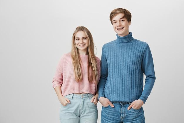 Красивая молодая пара позирует в помещении, держа руки в карманах