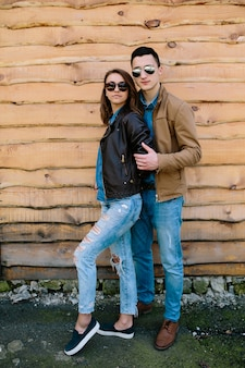 木製の壁を越えてポーズ美しい若いカップル