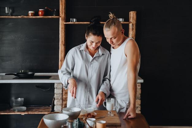 Красивая молодая пара вместе готовит здоровую еду, проводя свободное время дома.