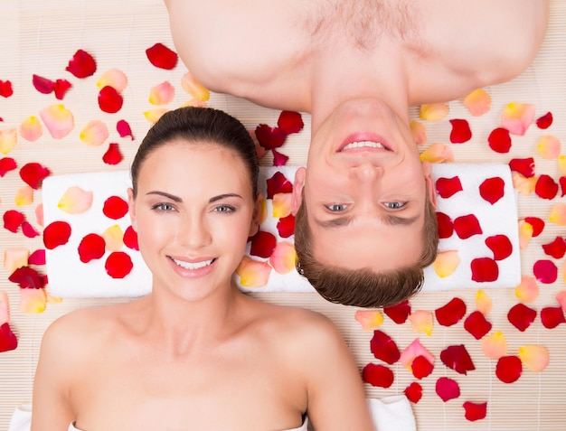 Красивая молодая пара расслабляется, лежа в лепестках роз.