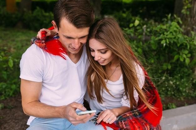 公園でリラックスしてスマートフォンを見て美しい若いカップル