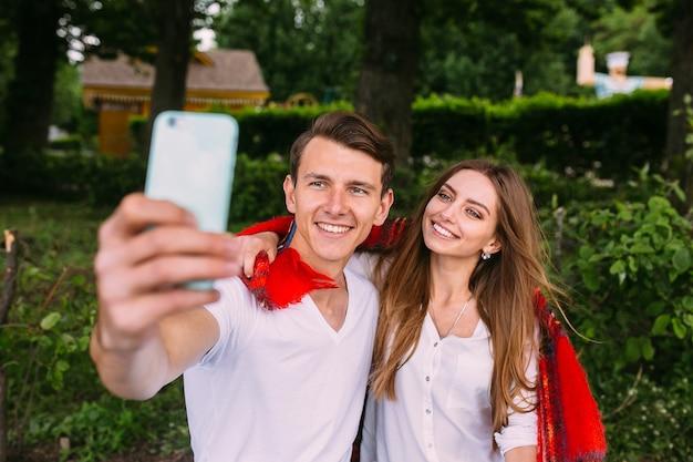 Красивая молодая пара отдыхает в парке и делает селфи