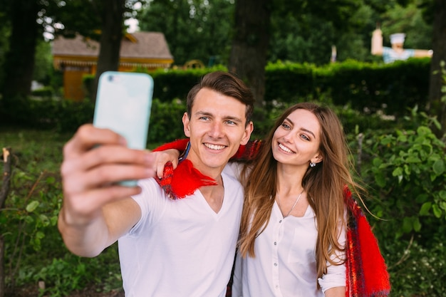 Beautiful young couple relaxing in the park and makes selfie