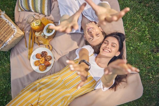 맛있는 식사와 오렌지 레모네이드와 함께 피크닉 시간에 쉬고 아름다운 젊은 부부