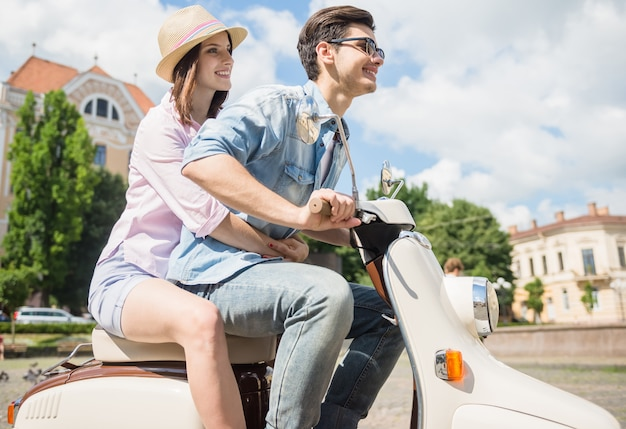 Beautiful young couple riding scooter together.
