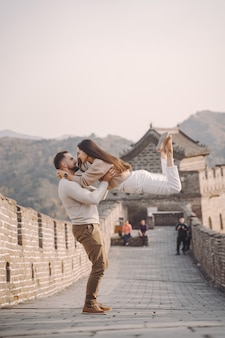 Beautiful young couple running and jumping at the great wall of china.