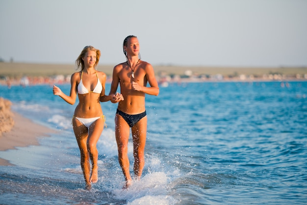 Beautiful young couple running at sea water edge and holding hands