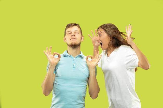 孤立した美しい若いカップルの半身像。男性は女性が叫んでいる間、目を閉じて落ち着きを保とうとしています。顔の表情、人間の感情の概念。