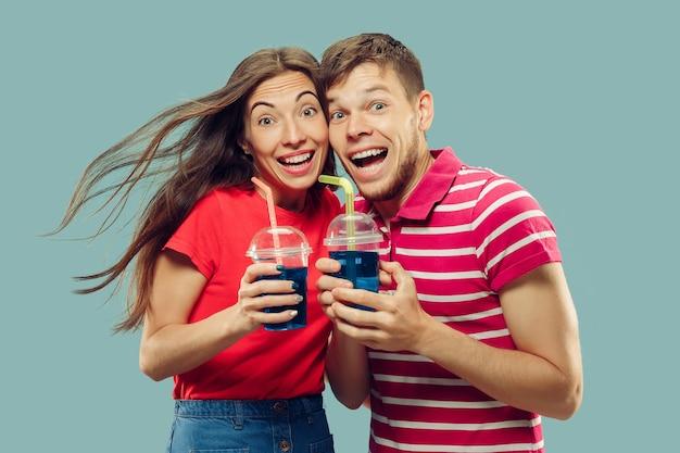 青で隔離の美しい若いカップルの半身像
