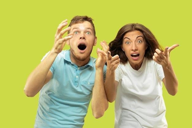 Поясный портрет красивой молодой пары, изолированные на зеленом пространстве. женщина и мужчина удивлены и шокированы блестящей новостью