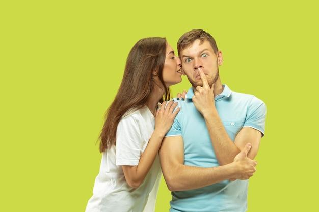Поясный портрет красивой молодой пары, изолированные на зеленом пространстве. женщина и мужчина стоят, обнимаются и целуются