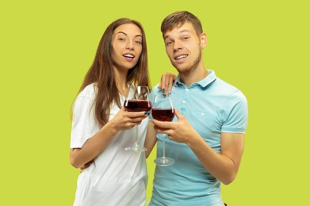 Поясной портрет красивой молодой пары на зеленом