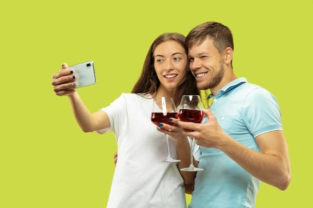 緑で隔離の美しい若いカップルの半分の長さの肖像画
