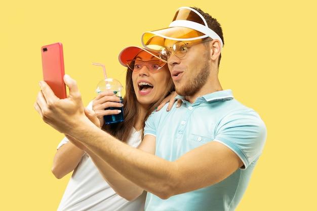 Поясный портрет красивой молодой пары, изолированный на желтом