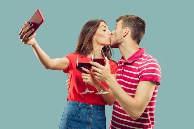 孤立した美しい若いカップルの半身像。笑顔の女性と男性がワインとグラスを持って自分撮りをしています。表情、夏、週末のコンセプト。