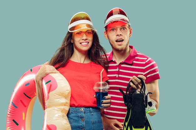 孤立した美しい若いカップルの半身像。水泳用品と帽子とサングラスで笑顔の女性と男性。表情、夏、週末のコンセプト。