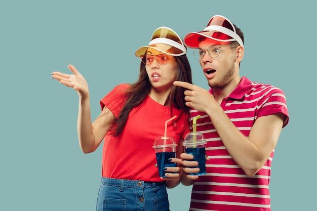Ritratto a mezzo busto della bella giovane coppia isolato. donna sorridente e uomo in berretti e occhiali da sole con bevande. espressione facciale, estate, concetto di fine settimana. colori alla moda.