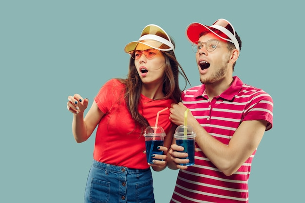 Beautiful young couple's half-length portrait isolated. smiling woman and man in caps and sunglasses with drinks. facial expression, summer, weekend concept. trendy colors.