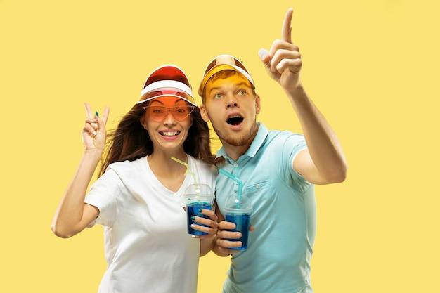 孤立した美しい若いカップルの半身像。カラフルなキャップで飲み物を持って立っている女性と男性。表情、夏、週末のコンセプト。トレンディな色。