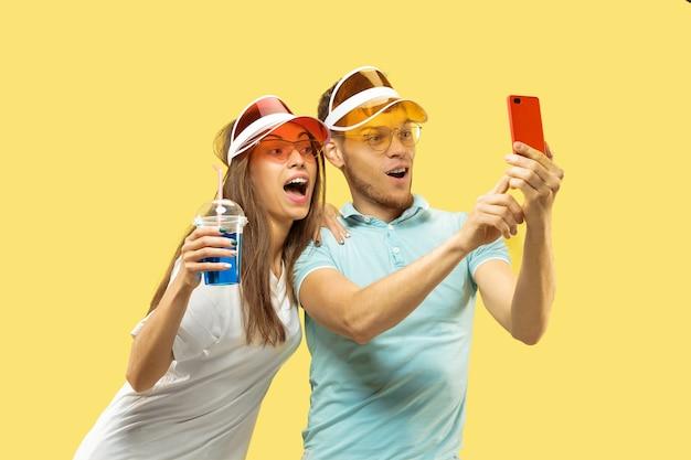 孤立した美しい若いカップルの半身像。自撮りをする飲み物を持って立っている女性と男性。表情、夏、週末のコンセプト。トレンディな色。