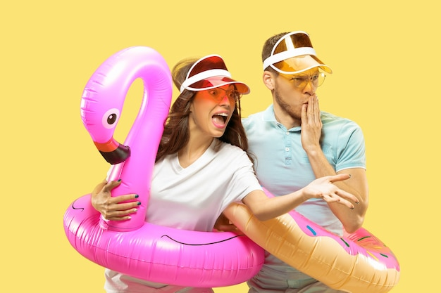 Beautiful young couple's half-length portrait isolated. woman and man in caps and sunglasses standing with swimming rings. facial expression, summer, weekend concept.