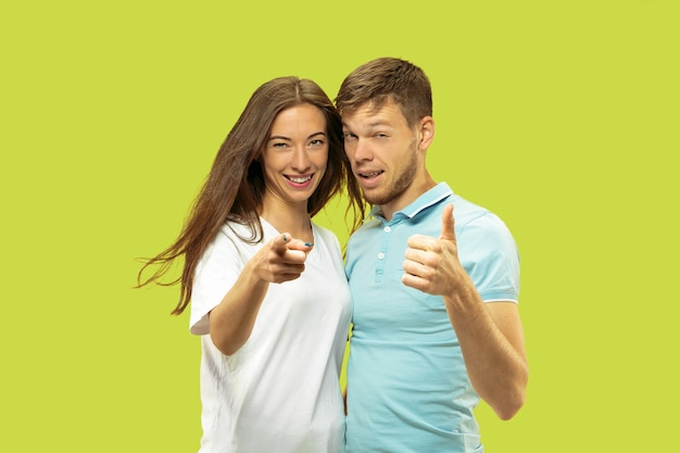 Beautiful young couple's half-length portrait isolated. woman and man standing and pointing up, showing the sing of ok. facial expression, human emotions concept.
