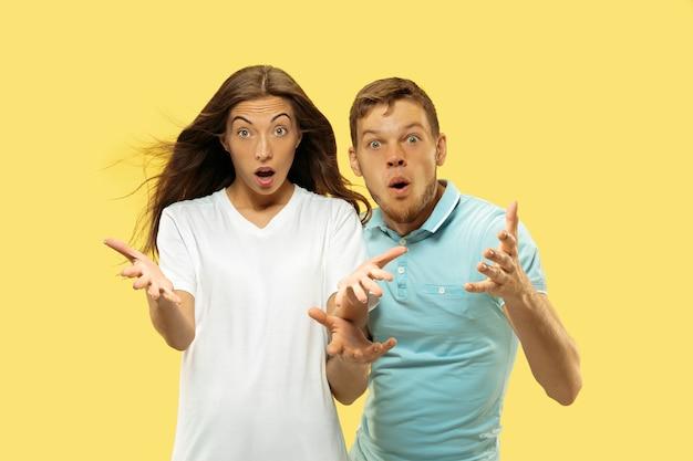 美しい若いカップルの半身像。何かを求めたりショックを受けたりするシャツを着た女性と男性。顔の表情、人間の感情の概念。トレンディな色。