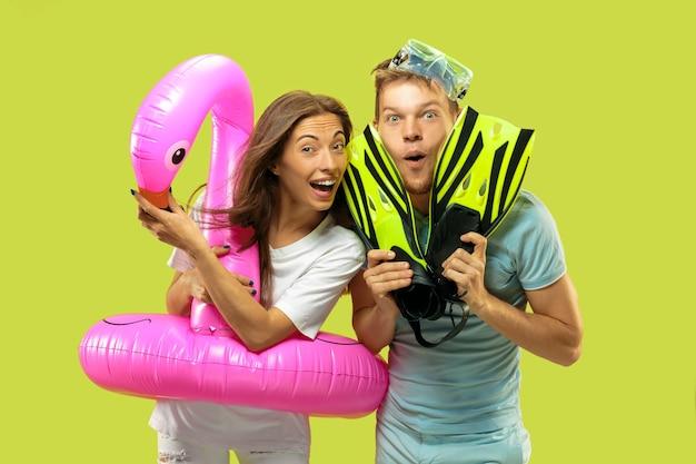 美しい若いカップルの半身像。フラミンゴと足ひれとしてピンクの浮き輪で立っている女性と男性。表情、夏、週末のコンセプト。