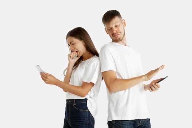 孤立した美しい若いカップルの肖像画。顔の表情、人間の感情。スマートフォンを持っている男女が画面が怖い。