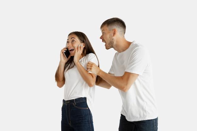 孤立した美しい若いカップルの肖像画。顔の表情、人間の感情。電話で話している女性、男性は自分自身に注意を払いたいと思っています。