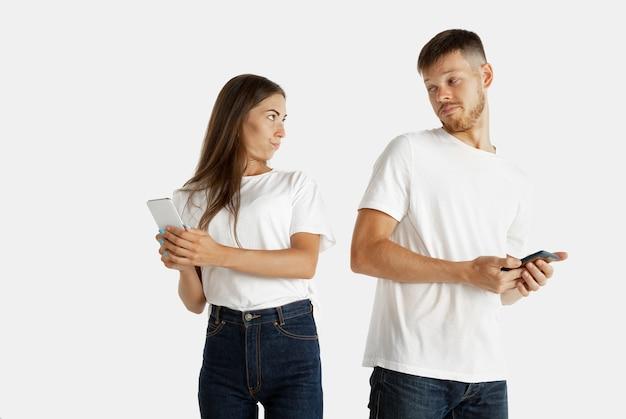 白いスペースに分離された美しい若いカップルの肖像画。顔の表情、人間の感情、広告の概念