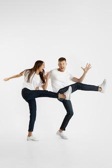 白いスタジオの背景に分離された美しい若いカップルの肖像画。顔の表情、人間の感情、広告のコンセプト。コピースペース。女性と男性が一緒にジャンプ、ダンス、または走っています。