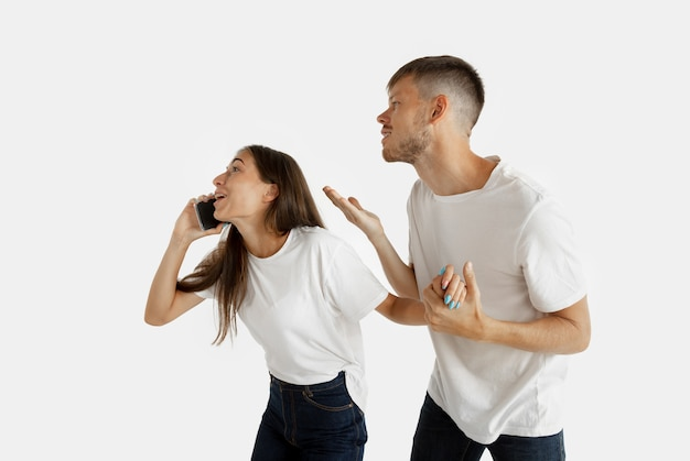白いスタジオの背景に分離された美しい若いカップルの肖像画。顔の表情、人間の感情、広告のコンセプト。電話で話している女性、男性は自分自身に注意を払いたいと思っています。