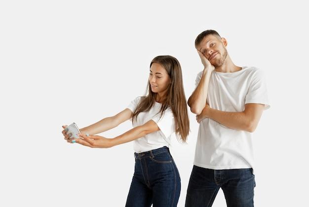 Ritratto della bella giovane coppia isolato su spazio bianco. espressione facciale, emozioni umane, concetto di pubblicità