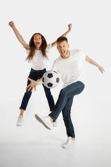 Ritratto di bella giovane coppia isolato su sfondo bianco studio. espressione facciale, emozioni umane, pubblicità, scommesse, concetto di sport. uomo e donna che giocano a calcio o calcio in azione.