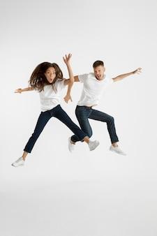 Ritratto di bella giovane coppia isolato sul muro bianco. espressione facciale, emozioni umane, concetto di pubblicità. copyspace. donna e uomo che saltano, ballano o corrono insieme.