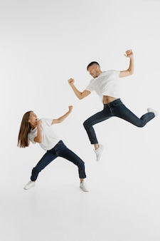 Beautiful young couple's portrait isolated on white wall. facial expression, human emotions, advertising concept. copyspace. woman and man jumping, dancing or running together.