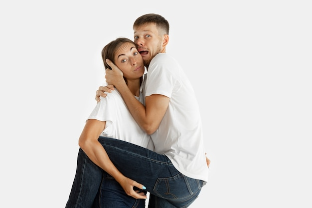 Beautiful young couple's portrait isolated on white wall. facial expression, human emotions, advertising, relation concept. man and woman holding each other, look scared, screaming.