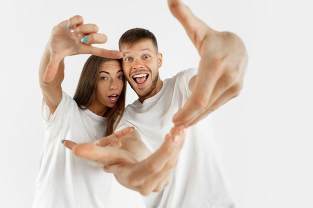 白いスタジオで美しい若いカップルの肖像画