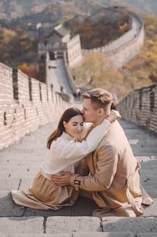 Красивая молодая пара, показывая любовь на великой китайской стене