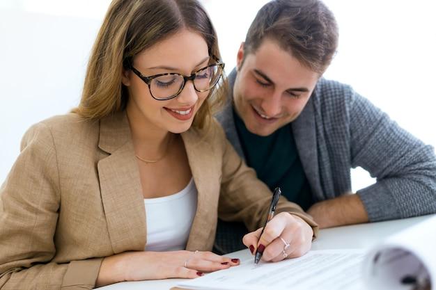 美しい若いカップルは、オフィスで財務契約を締結します。